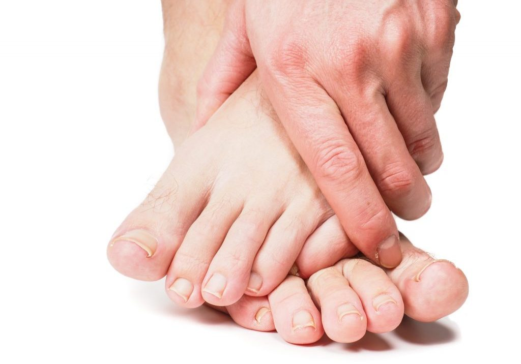 Male person holding onto feet isolated towards white